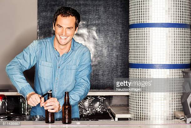 Bartender Opening Beer Bottle At Counter In Nightclub