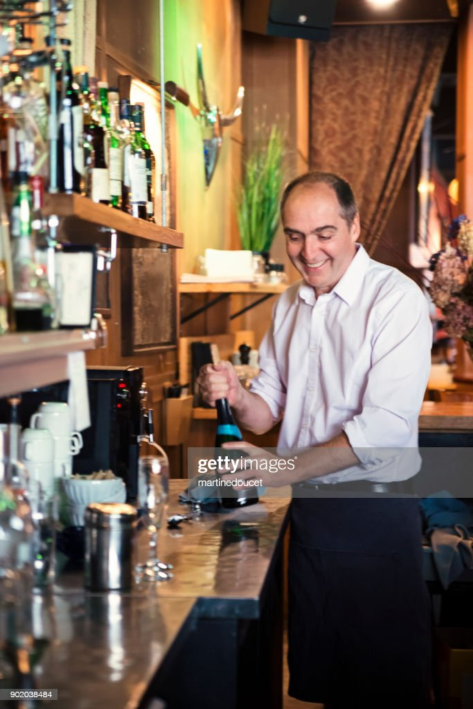 Bartender opening wine bottle behind a bar counter. : Stock Photo