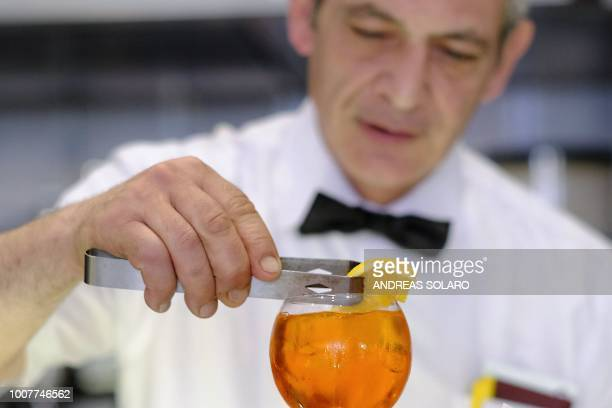 A bartender places a slice of orange as he prepares a Spritz cocktail in a cafe in central Rome on July 17 2018 Aperol is a historical brand which...
