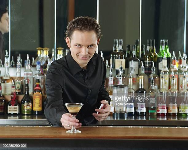 Bartender placing cocktail on bar, smiling, portrait