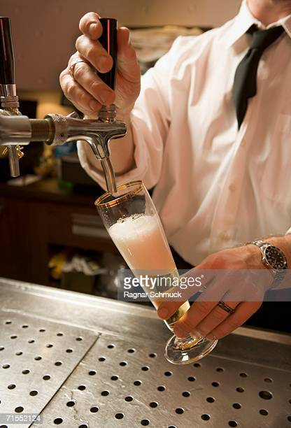 bartender pouring a beer from tap - ビールサーバー ストックフォトと画像