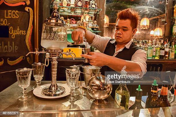 CONTENT] bartender pouring absinthe the traditional way Bangkok Thailand