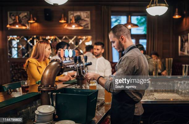 bartender pouring beer for customers in pub - facial hair stock pictures, royalty-free photos & images