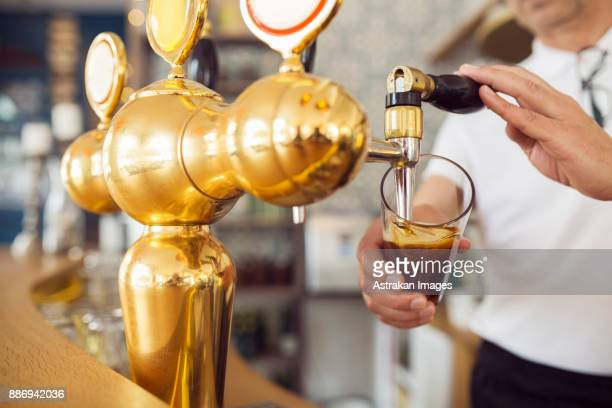 bartender pouring beer into beer glass - ビールサーバー ストックフォトと画像