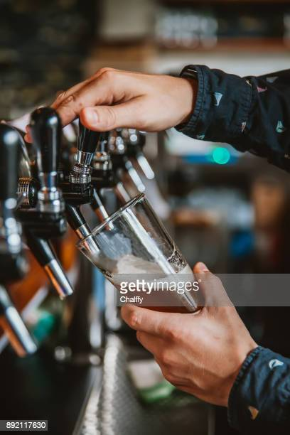 bartender pouring beer - ale stock pictures, royalty-free photos & images