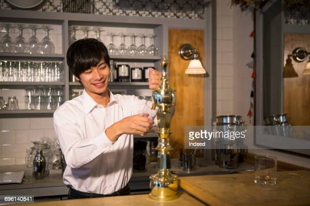 Bartender pouring beer to glass