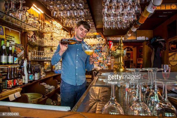 Bartender pouring Belgian beer in glass in Flemish cafe 't Brugs Beertje in Bruges / Brugge, West Flanders, Belgium.
