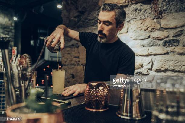 bartender pouring cocktail in a glass - bartender stock pictures, royalty-free photos & images
