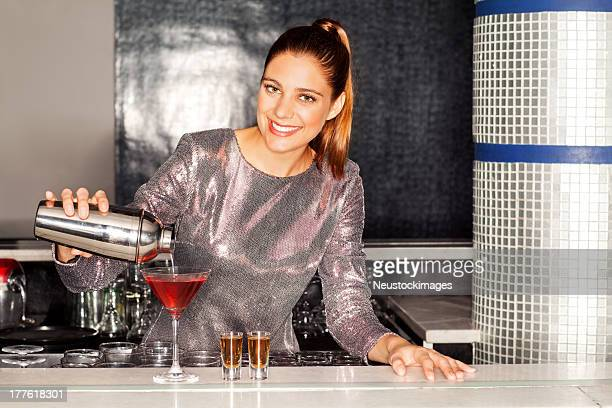 Bartender Pouring Cocktail In Glass At Bar Counter