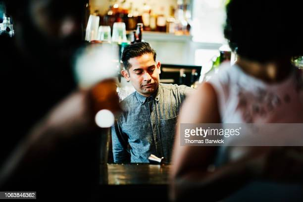bartender pouring drinks in crowded bar - bartender stock pictures, royalty-free photos & images