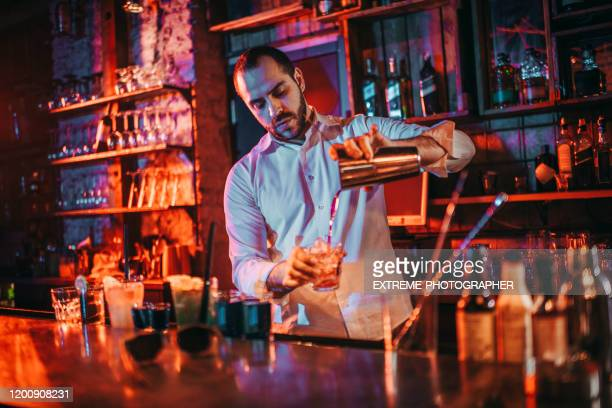 bartender pouring drinks into shot glasses from a drink shaker in a pub - bartender stock pictures, royalty-free photos & images