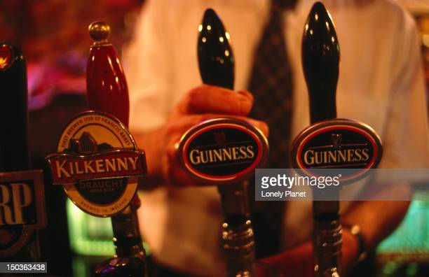 Bartender pouring pint of Guinness from beer tap at bar in O'Donoghue's.
