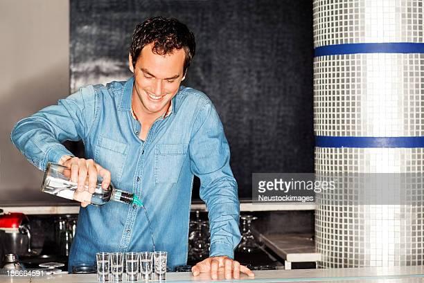 Empregado de Bar Verter Vodca em Tiro óculos no balcão de Bar