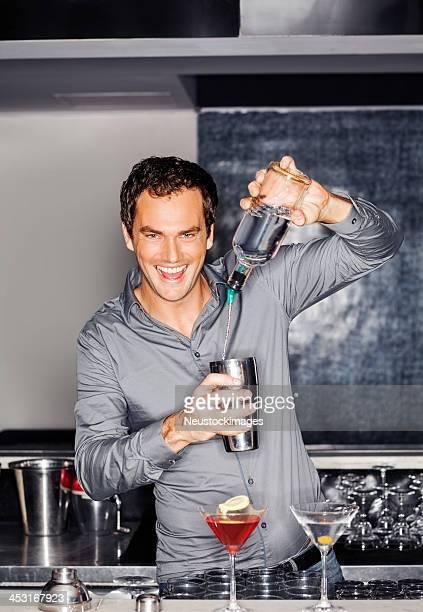 Bartender Pouring Vodka Into Shaker At Bar Counter