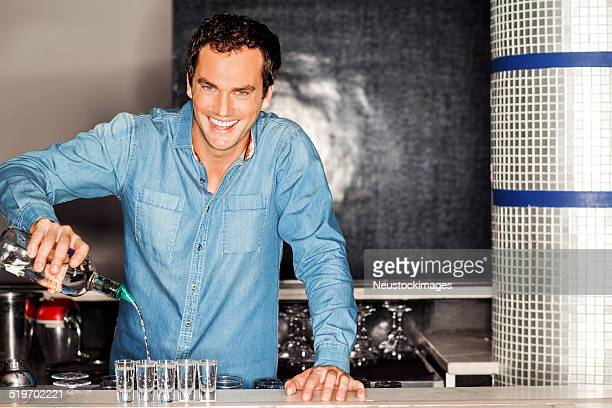 Bartender Pouring Vodka Into Shot Glasses At Counter In Nightclu