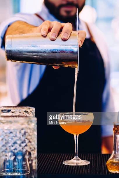 bartender pouring whiskey cocktail into glass with sugared rim - bartender stock pictures, royalty-free photos & images
