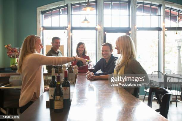 Bartender pouring wine at bar