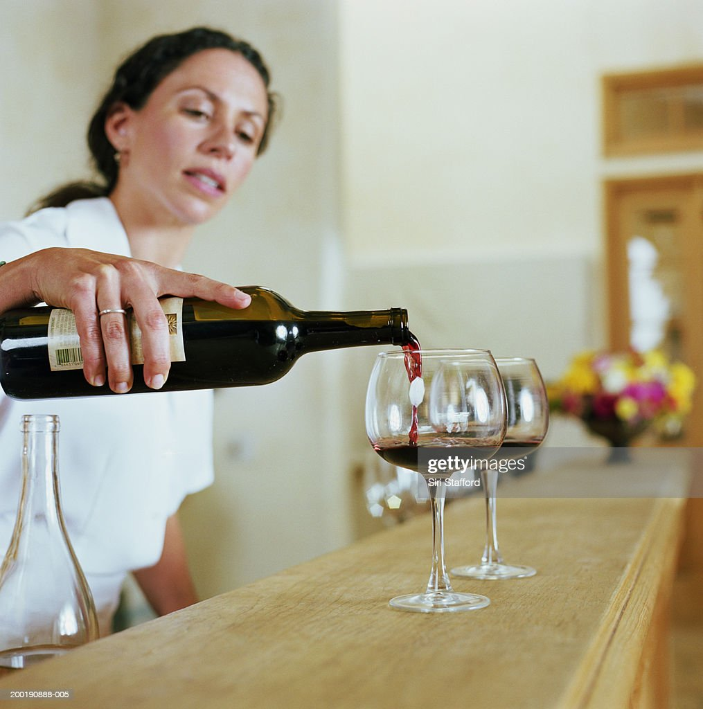 Bartender pouring wine into glass : Stock Photo