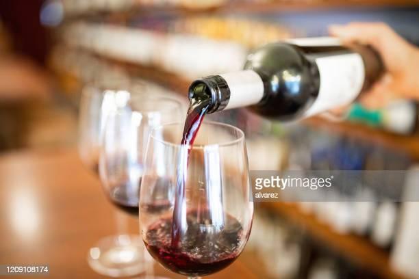 グラスにワインを注ぐバーテンダー - ワインセラー ストックフォトと画像