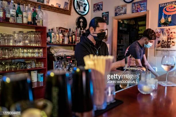 Bartender pours a beer at a bar in Berlin's Prenzlauer Berg district on October 10, 2020. - Stolz, along with other bar owners in Berlin, has...