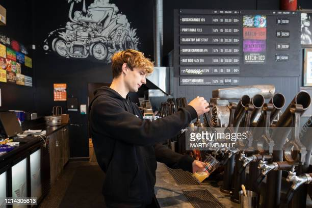 Bartender pours a beer on the first day of re-opening after establishments were shut for two months due to the COVID-19 coronavirus outbreak in...