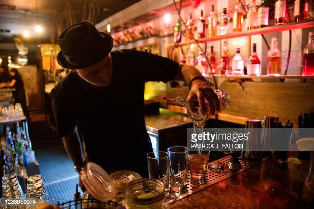 Bartender pours a cocktail for fully vaccinated customers at the bar inside Risky Business, a private members-only club, that was once The Other Door...