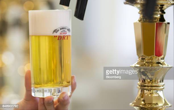 A bartender pours a glass of Asahi Super Dry beer from a beer tap at the Asahi Kanagawa Brewery operated by Asahi Breweries Ltd a unit of Asahi Group...