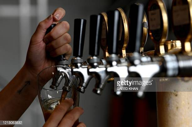 A bartender pours a glass of beer for a customer at a resturant in Sydney on May 15 2020 Sydney's bars and restaurants flung open their doors as a...