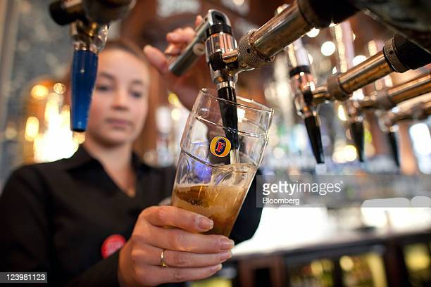 A bartender pours a pint of Fosters lager at The Knights Templar public house operated by JD Wetherspoon Plc in London UK on Wednesday Sept 7 2011 UK...