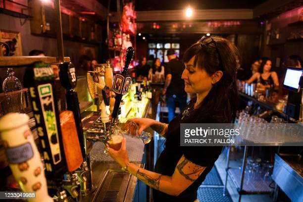 Bartender pours beers for fully vaccinated customers at the bar inside Risky Business, that was once The Other Door but closed during the Covid-19...