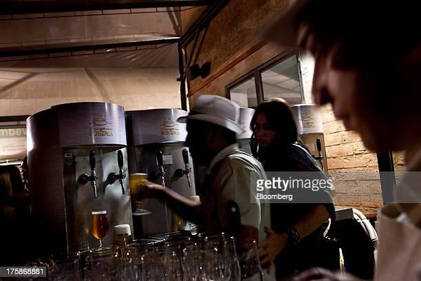 A bartender pours glasses of Cia de Bebidas das Americas Bohemia brand beer at a restored Bohemia brewery in Petropolis Brazil Sunday Aug 4 2013...