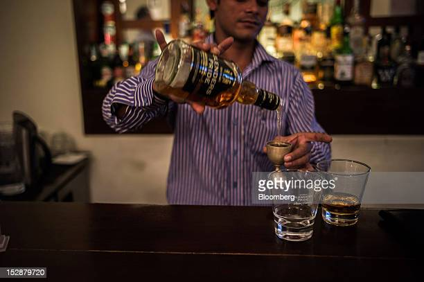 A bartender pours Pernod Ricard SA's Blender's Pride whiskey into a measuring cup at a bar in New Delhi India on Thursday Sept 27 2012 Diageo Plc...