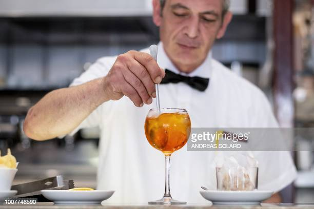 A bartender prepares a Spritz cocktail in a cafe in central Rome on July 17 2018 Aperol is a historical brand which has existed since 1919 and had a...