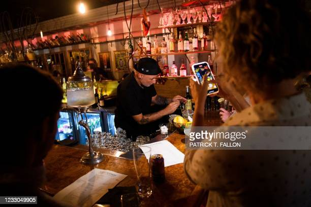Bartender prepares absinthe for fully vaccinated customers at the bar inside Risky Business, a private members-only club, that was once The Other...