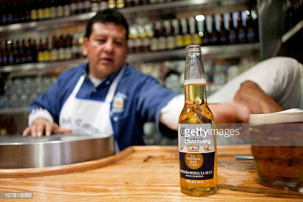 A bartender prepares to serve a Grupo Modelo SAB brand Corona beer along with a Modelo draft beer at a brew pub in Mexico City Mexico on Tuesday Dec...