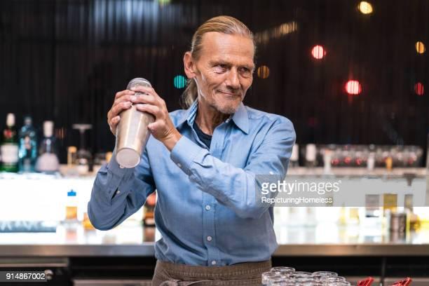 barmann bereitet ein getränk mit einem cocktail-shaker zu - repicturing homeless stock-fotos und bilder