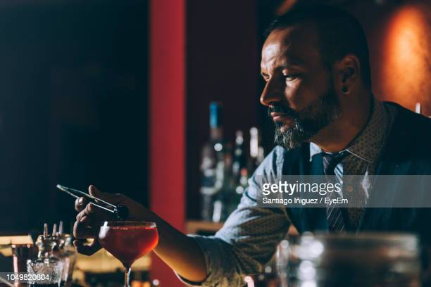 bartender preparing cocktail in bar - bartender stock pictures, royalty-free photos & images