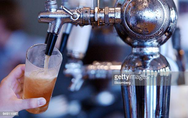A bartender pulls a glass of draft beer from a condensationcovered spigot at a bar in Melbourne January 2 2004 Coles Myer Ltd Australia's biggest...
