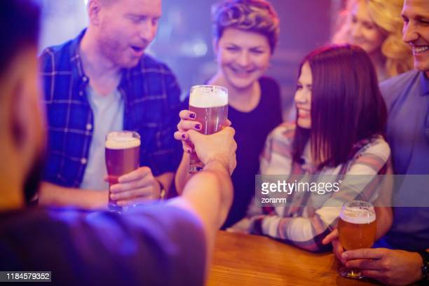 bartender reaching woman in crowd with glass of draft beer - passing giving stock pictures, royalty-free photos & images