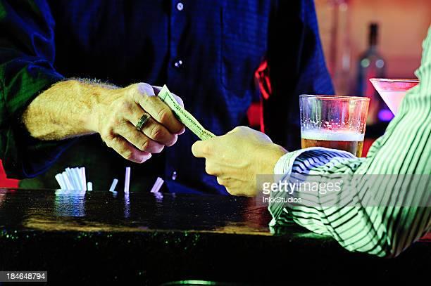 Bartender Receiving Cash at the Bar