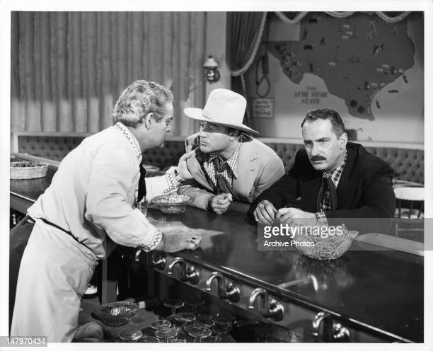 Bartender Rod O'Connor offers information to Red Skelton as Keenan Wynn sits bored in a scene from the film 'Texas Carnival' 1951