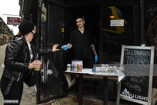 Bartender sells a frozen margarita to go to a customer in the Bushwick neighborhood on April 2, 2020 in New York City. Currently, over 92,000 people...
