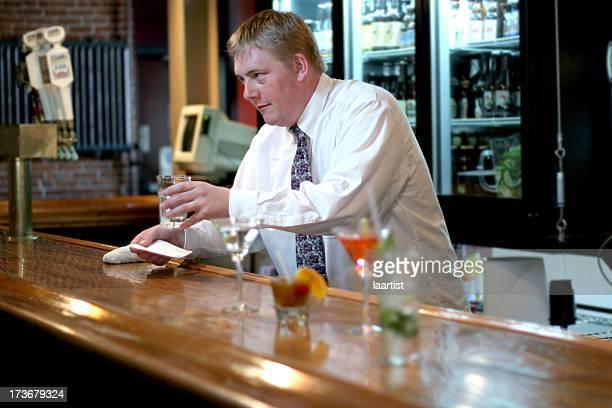Bartender serves a drink.