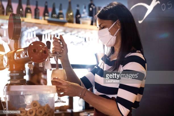 bartender serviert ein frisches bier in einem pub - corona beer stock-fotos und bilder