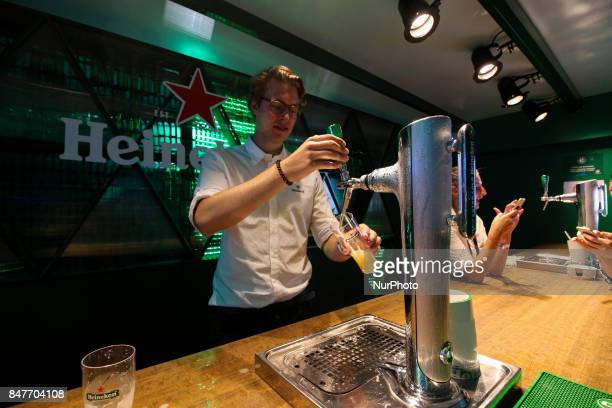 Bartender serves Heineken beer on the official Heineken brewery cabin at Rock in Rio The bartenders team came from the Netherlands to attend the VIP...
