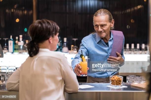 ein barmann serviert einer frau ein getränk - repicturing homeless stock-fotos und bilder