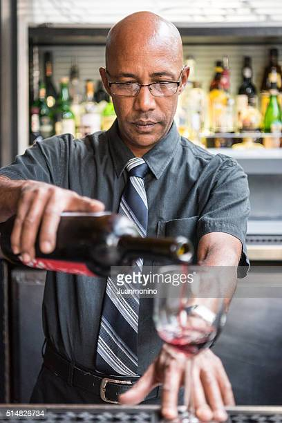 Bartender serving a glass of red wine