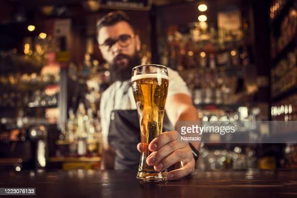 bartender serving beer - bartender stock pictures, royalty-free photos & images
