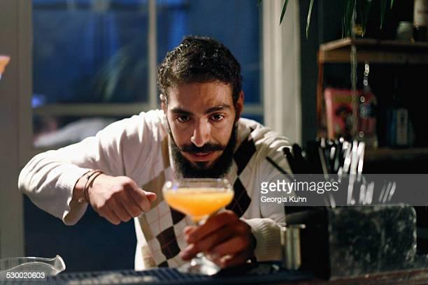 Bartender serving cocktail at bar