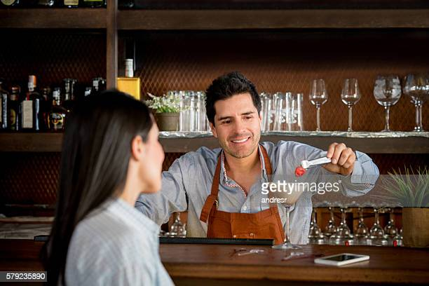 Bartender serving cocktail to a customer